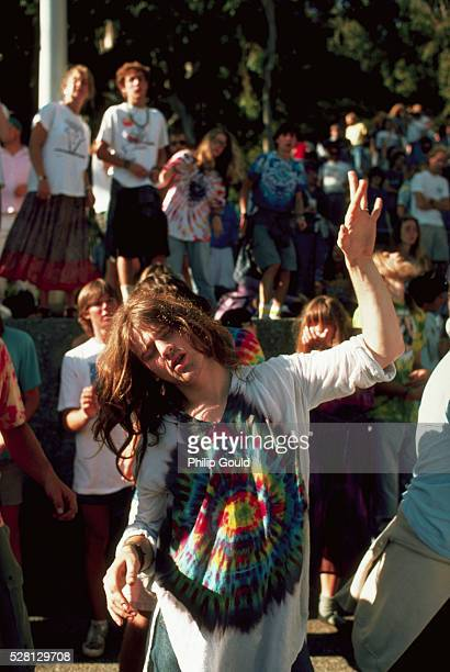 Wearing a tiedyed shirt a concertgoer dances to the music of the Grateful Dead in concert at Berkeley's Greek Theater California USA