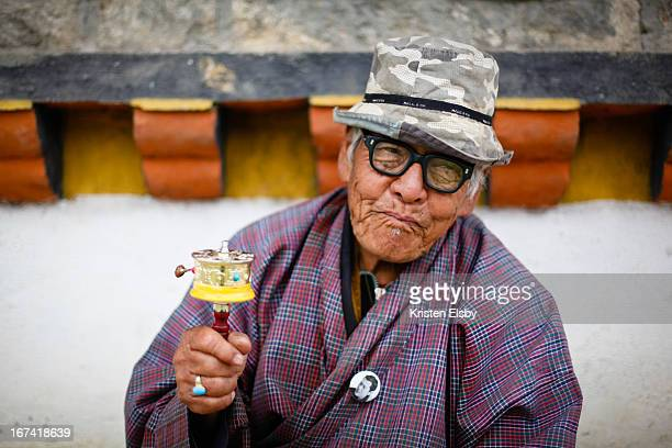 Wearing a traditional gho and a badge featuring the King of Bhutan's portrait, an elderly man prays and chants mantras while spinning a mani wheel at...