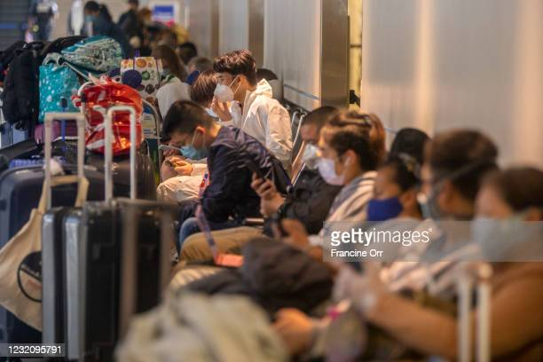 Wearing a tyvek suit, Ryan Wang middle, is sitting in a crowded seating area as he waits for a flight at LAX on Friday, April 2, 2021 in Los Angeles,...