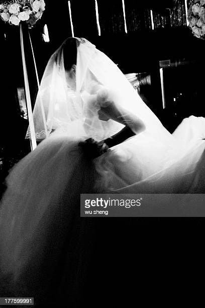 Wearing a wedding dress woman, have a beam of light on her.