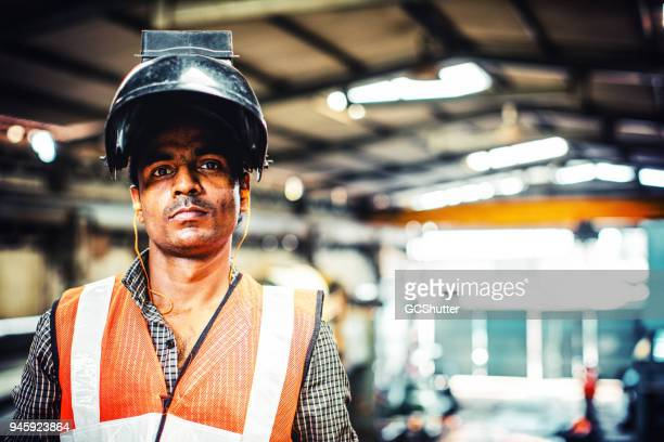 wearing a welder mask while looking at the camera - welding stock photos and pictures