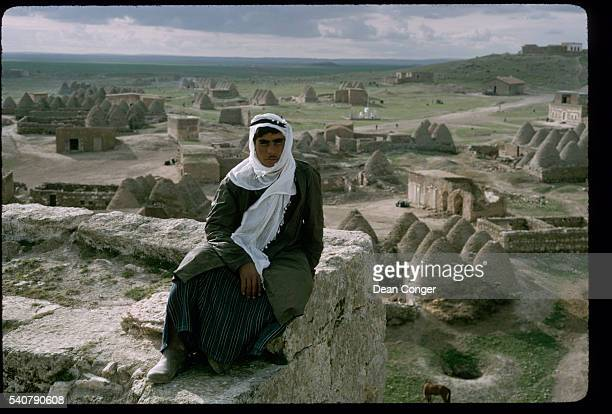 Wearing a white kaffiyeh a Harran resident sits atop a ruin overlooking the village and beehiveshaped mud houses