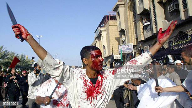 Wearing a white shroud a Shiite Muslim pilgrim holds up his arms as he takes part in self flagellation during lamentation ceremonies in the southern...