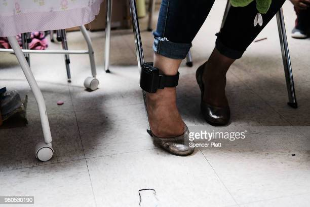 Wearing an ankle monitor bracelet a woman who identified herself as Jennifer sits at the Catholic Charities Humanitarian Respite Center after...