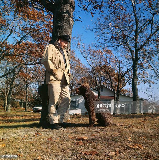 """Wearing an old skipper's cap, John Steinbeck enjoys a stroll with his famous French Poodle, """"Charley."""" The pooch is the """"hero"""" of the best-selling..."""