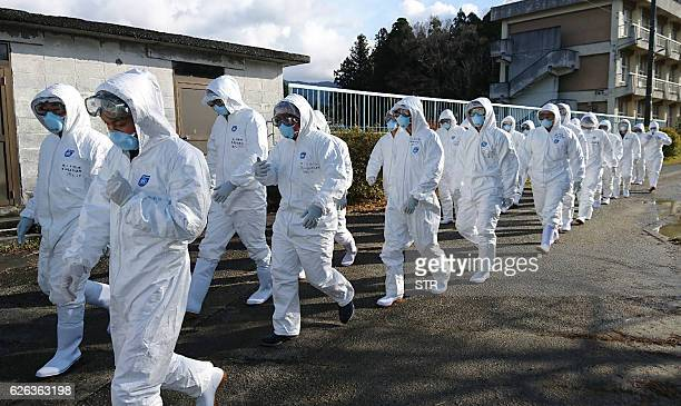 TOPSHOT Wearing antivirus suits soldiers of the Ground Self Defense Force head for chicken farm in Sekikawa Niigata prefecture on November 29 2016...