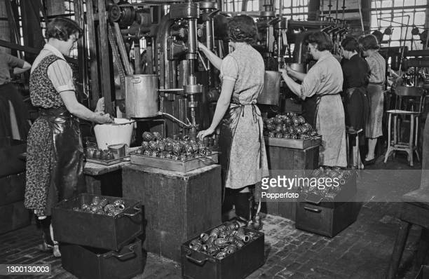 Wearing aprons, female munitions workers drill the threads of hand grenades , a fragmentation grenade for the British Army, at a munitions factory in...