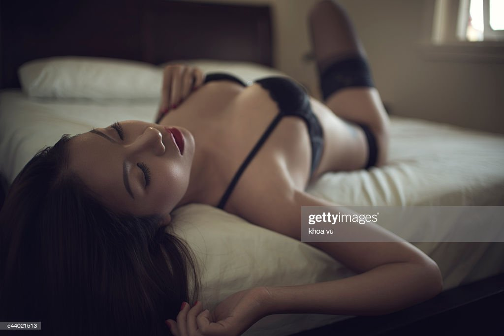 Wearing black lingerie in bed : Stock Photo
