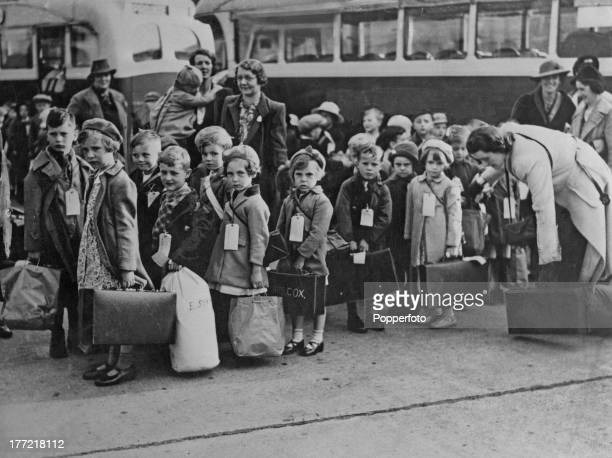 Wearing card labels British evacuee children queue in front of buses on their way to new homes during World War II circa 1940