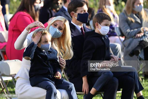 Wearing face masks to reduce the risk posed by the coronavirus pandemic, Ivanka Trump sits with her son Theodore Kushner and her husband Jared...