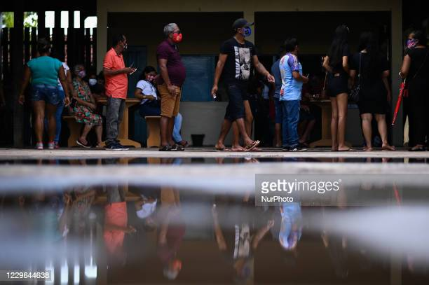 Wearing face protection masks, voters wait in line to vote during municipal elections amid the Coronavirus pandemic in Santana, Amapá State, Brazil,...