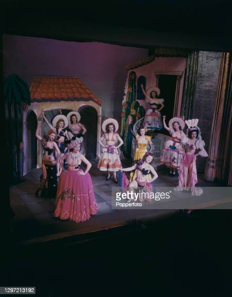 Wearing flamboyant costumes, various female dancers, including Anita D'Ray kneeling, pose on stage at the Windmill Theatre in Great Windmill Street,...