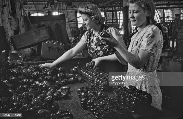 Wearing floral aprons, two female munitions workers inspect and examine recently cast hand grenade casings, a fragmentation grenade known as a Mills...