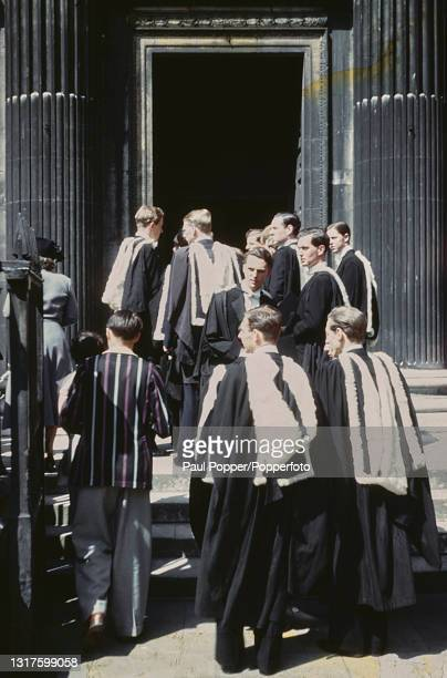 Wearing full academic dress comprising gown, hood and headdress, a group of graduates enter the Senate House for a graduation ceremony on Degree Day...