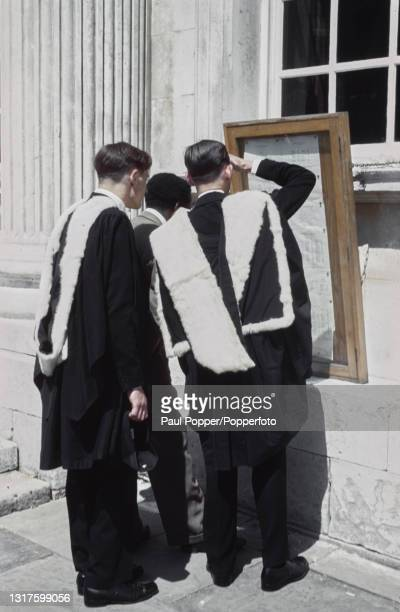 Wearing full academic dress comprising gown, hood and headdress, three graduates study degree exam results pinned to a board outside Senate House on...