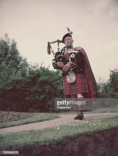 Wearing full highland dress Piper to the Sovereign Alexander MacDonald of the Scots Guards plays a Great Highland bagpipe in June 1953
