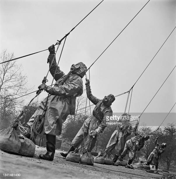 Wearing gas mask respirators and full protective clothing, members of a barrage balloon unit from RAF Balloon Command pull on ropes to tighten up...