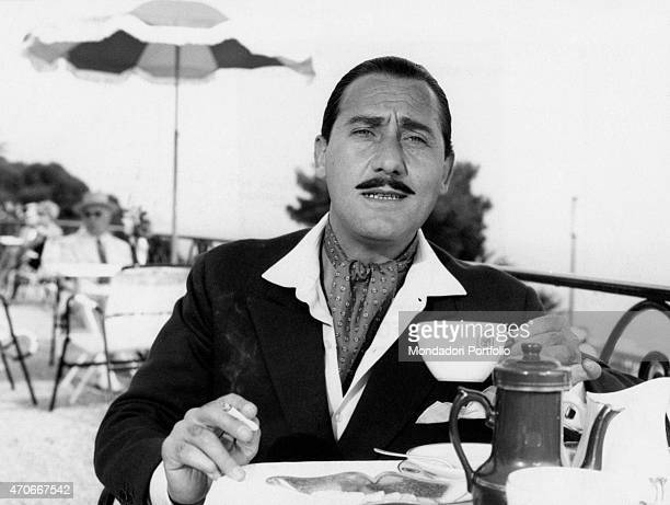 'Wearing gentlemanly garments and a foulard around his neck the Italian star performer Alberto Sordi is having breakfast on the terrace of a...