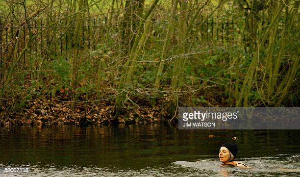 Wearing gloves and a wool cap Sarah Saunders braves the cold during a swim in the Women's Bathing Pond on Hampstead Heath 18 January 2005 in London...