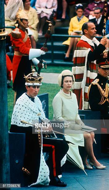 Wearing gold coronet and robe and holding sceptre of his authority Prince Charles newly invested Prince of Wales sits with his mother Queen Elizabeth...