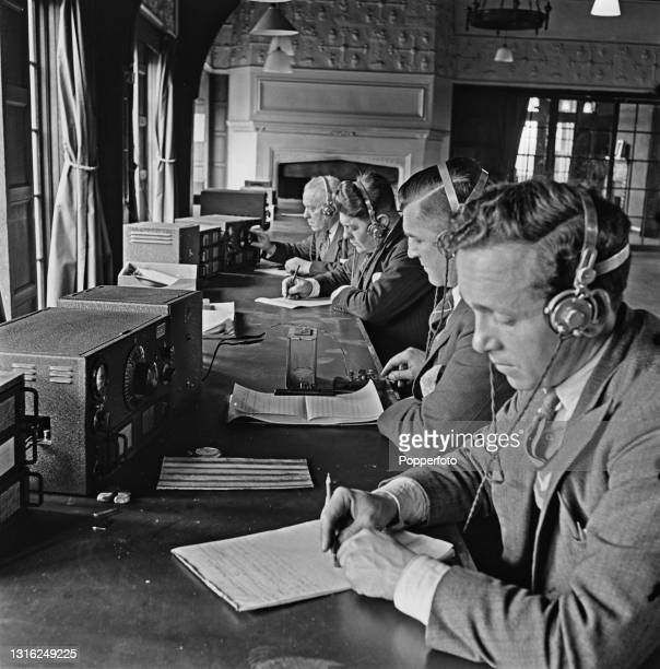 Wearing headphones, civil servants take notes as they listen in to foreign news radio broadcasts on receivers in the wireless section of the...