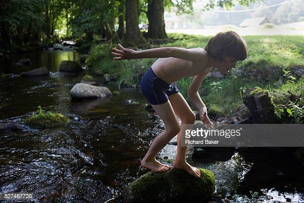 Wearing his bathing costume a young adventurer clambers over rocks in the Gross Enz river in Germany's Black Forest The lad of 10 crouches to better...
