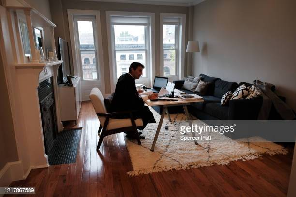 Wearing his official robe, New York City Criminal Court Judge Paul McDonnell works remotely from his Brooklyn apartment due to the coronavirus...