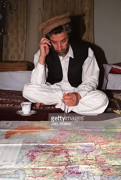 Wearing his trademark brown Afghan woollen hat the Afghan opposition's veteran military commander Ahmad Shah Masood uses 28 June 2001 his cellular...