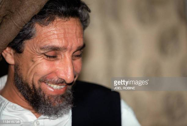 Wearing his trademark brown Afghan woollen hat the Afghan opposition's veteran military commander Ahmad Shah Masood converses 28 June 2001 with an...