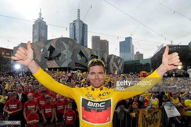 Wearing his winner's yellow jersey, Tour de France winner Cadel Evans of Australia gives the thumbs-up in front of thousands of fans which lined the...