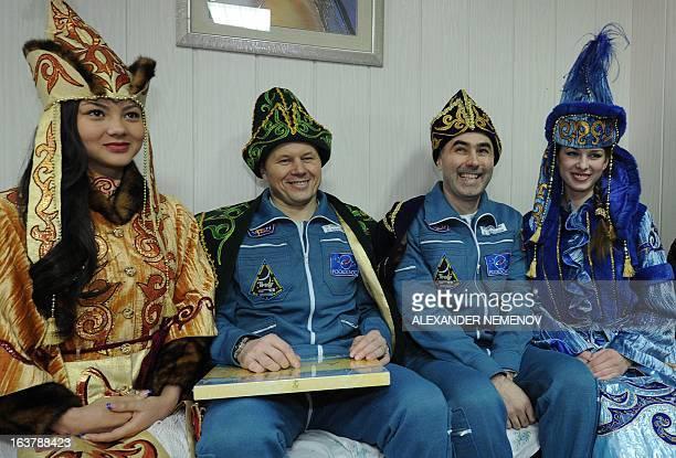 Wearing Kazakh traditional costumes Russian Soyuz Commander Oleg Novitskiy and Russian Flight Engineer Evgeny Tarelkin pose for a photo with Kazakh...
