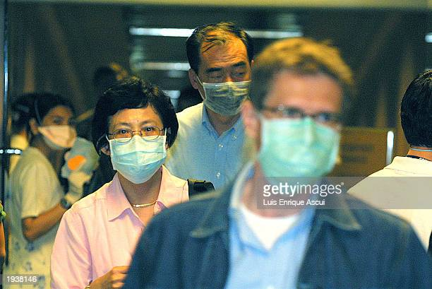 Wearing masks, passengers arriving from Hong Kong walk past an 'Infrared Fever Screening System' April 18, 2003 at Singapore's Changi Airport in...