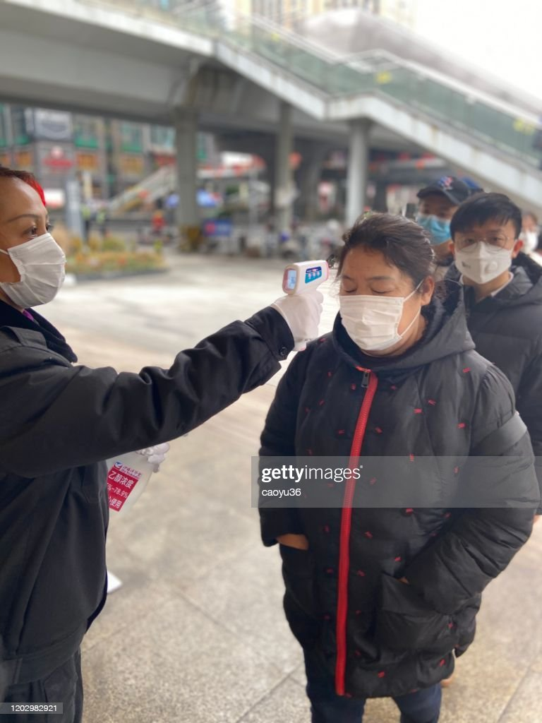 Wearing masks, people lined up for temperature checks before entering the mall in Chengdu,China : Stock Photo