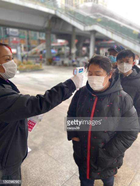 wearing masks, people lined up for temperature checks before entering the mall in chengdu,china - temperature checkpoint stock pictures, royalty-free photos & images