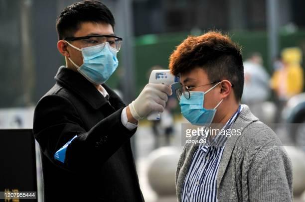 usando máscaras, as pessoas fizeram fila para verificações de temperatura antes de entrar no shopping 'starbacks e hotel em chengdu, china - wuhan - fotografias e filmes do acervo