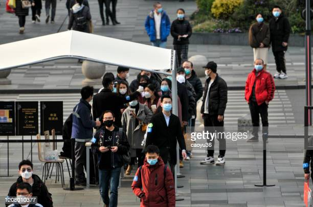 マスクを着用し、中国成都のモール「スターバックス」と「ホテル」に入る前に温度チェックのために並ぶ人々 - スターバックス ストックフォトと画像
