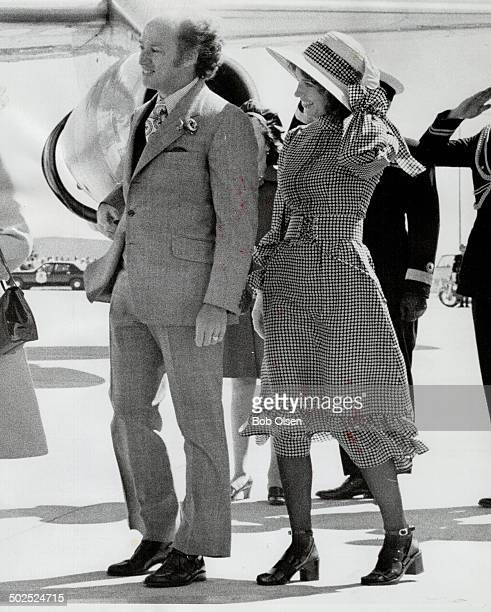 Wearing midi-dress with brown-and-white checks high neck; corsetted waist and a flaring skirt; Mrs. Margaret Trudeau walks with her husband. Primi...