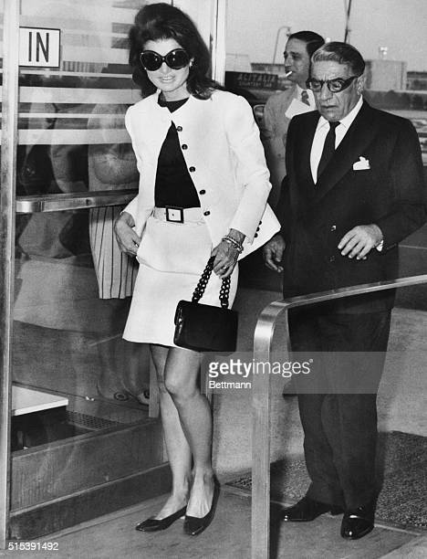 Wearing mod sunglasses and a miniskirt, Jacqueline Kennedy Onassis accompanies her husband, Aristotle, to a plane at Kennedy Airport on today, before...