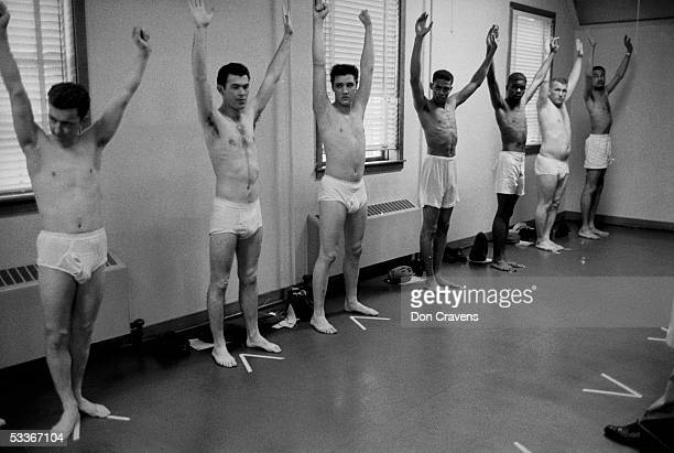 Wearing only underwear, singing star turned US Army Pvt. Elvis Presley raises his arms along with several other inductees during an inspection at Ft....