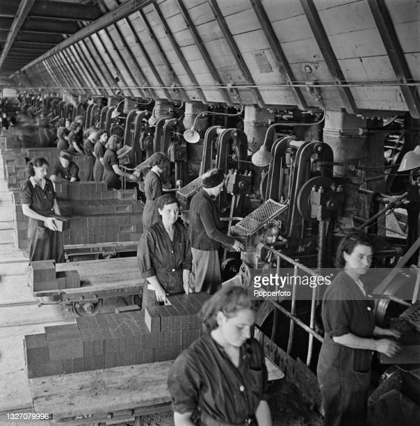 Wearing protective boiler suits, female brick workers operate presses to produce clay bricks prior to firing in kilns at a London Brick Company...