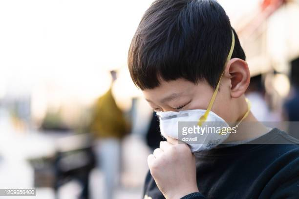 wearing protective mask in city - korea stock pictures, royalty-free photos & images