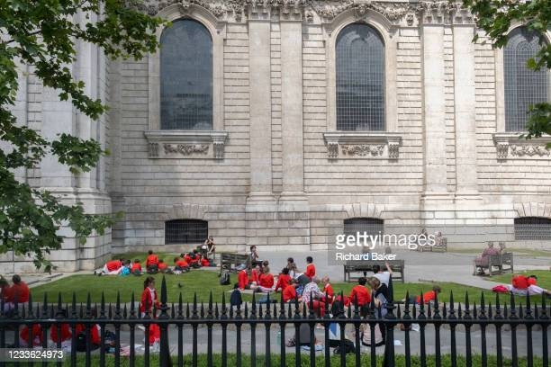 Wearing red school uniform jumpers, a group of school children enjoy warm sunshine during a day of outdoor learning beneath Wren architecture of St...