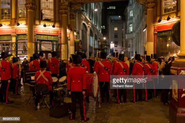Wearing red uniforms a military band takes a breather between musical evening to help with the Poppy Appeal in Leadenhall Market in the Square Mile...