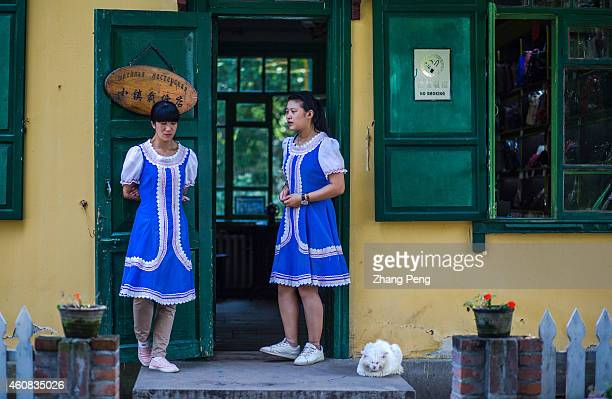 Wearing Russian styled skirts two Chinese girls stand at the door of a traditional tailor shop On the Sun Island a famous scenic spot in Harbin there...