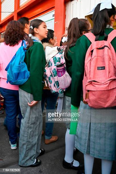 Wearing school uniform pants first year high school student Lian Estrella Gonzalez waits in line to enter her school in Mexico City on August 26 2019...