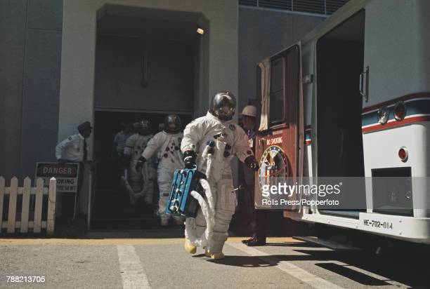 Wearing space suits the Apollo 16 crew of NASA astronauts Commander John Young Lunar Module pilot Charles Duke and Command Module pilot Ken Mattingly...