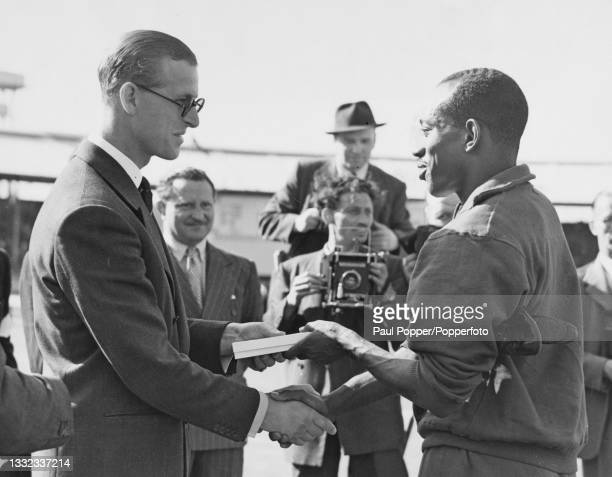 Wearing sunglasses, Prince Philip, Duke of Edinburgh shakes hands with American sprinter Harrison Dillard as he presents the athlete with a plaque...