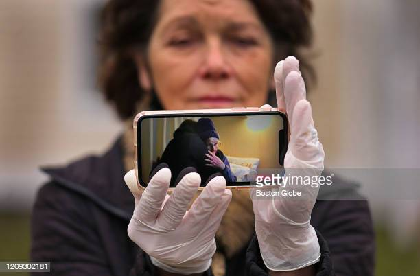 Wearing surgical gloves Carol Pouliot cradles her phone with a photo of her hugging her mom in her room at a Worcester nursing home a month ago on...