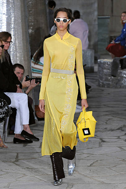 bcd5ff3789 Wearing the latest yellow color trend, a model walks the Loewe fashion show  runway at