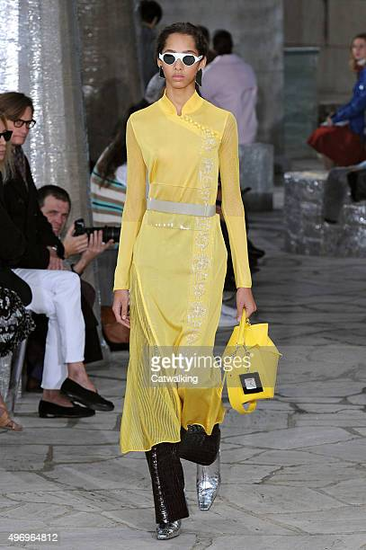 Wearing the latest yellow color trend a model walks the Loewe fashion show runway at the spring summer 2016 women's readytowear fashion weeks during...